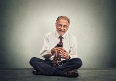 stock-photo-82294227-senior-man-sitting-on-floor-using-smart-phone-texting